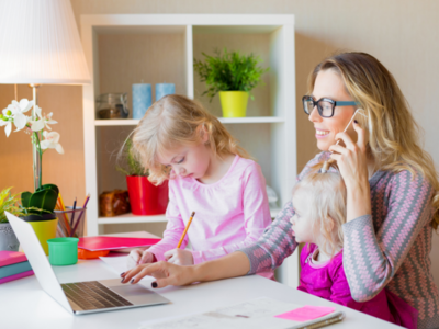 Image of mother with two children while working at home